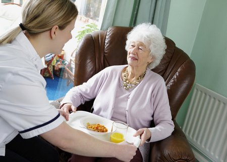 Carer providing food on a tray in clients house